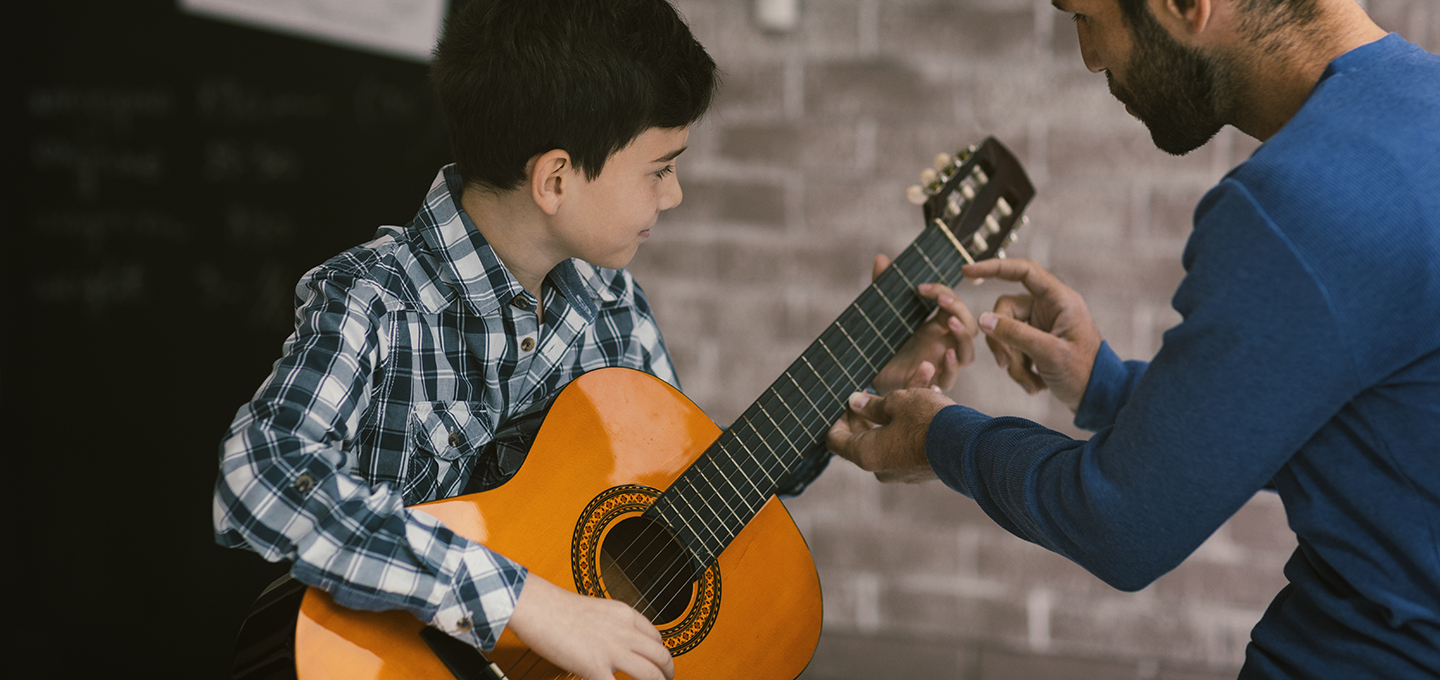 child playing guitar with instructor helping