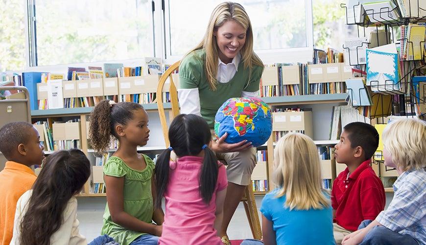 teacher showing map of world to children