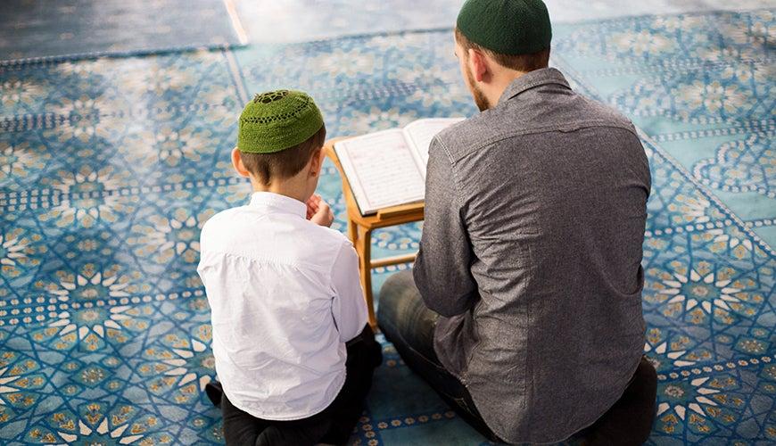 Boy at Mosque reading Koran with parent or teacher