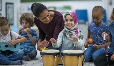 child plays drums with teacher and other children