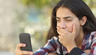 teenage girl recoiling at something on her mobile phone