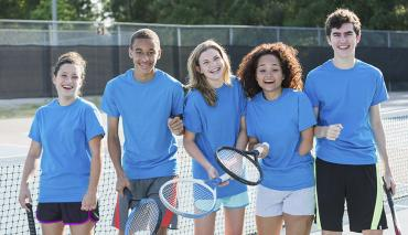 Young people at tennis lesson